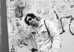 Olivier Zahm in front of his caricature in the Jean-Philippe Delhomme drawing…