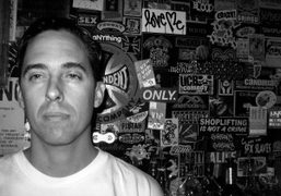 Erik Foss in front of his sticker wall at his bar Lit…