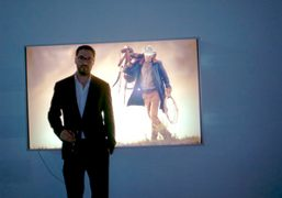 Adam Kimmel in front of a photo of Dan Colen from his…