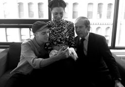 Kaws and Simon de Pury look at pictures in China Chow's iPhone…
